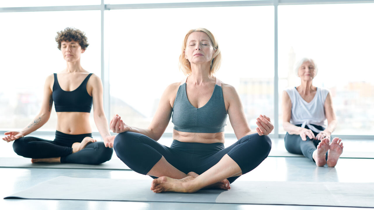 Mature women performing yoga breath exercises