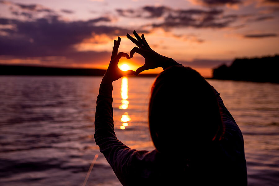 Soul Yoga Workshops represented by heart-shaped fingers over a sunset